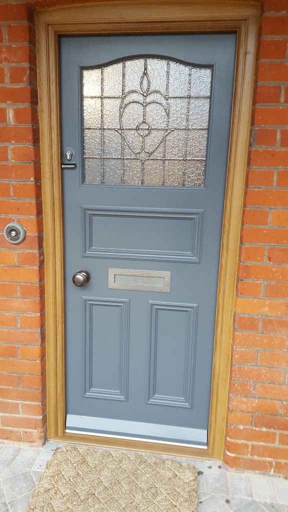 Dark-grey-panelled-door-with-patterened-lead-glass-e1538726449996-576x1024